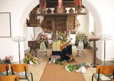 Bestattung: eine Sagaufbahrung mit Blumen und Kerzen