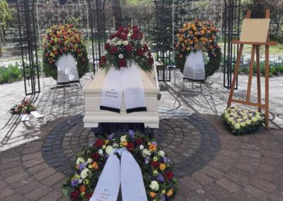 Bestattung: eine Sargaufbahrung mit Blumen