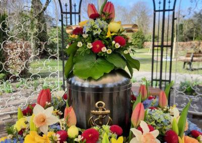 Bestattung: eine Urnenaufbahrung mit sehr vielen bunten Blumen