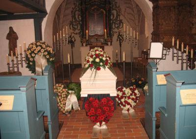 Bestattung: eine Sargaufbahrung mit Blumen und Kerzen