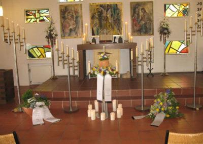 Bestattung: eine Urnenaufbahrung mit Blumen und Kerzen