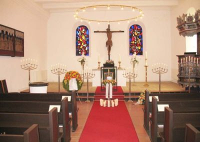 Bestattung: eine Urnenaufbahrung mit Blumen und vielen Kerzen