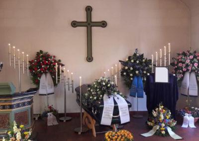Bestattung: eine Sargaufbahrung mit Blumen und vielen Kerzen