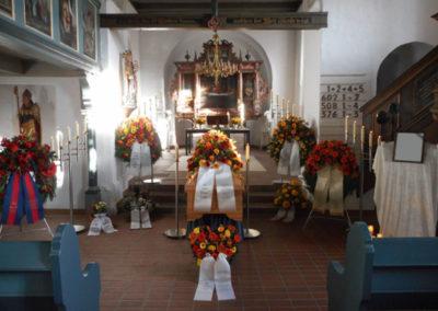 Bestattung: eine Sargaufbahrung mit sehr vielen Blumen und einigen Kerzen