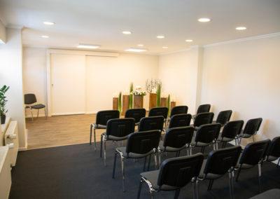 Trauerhalle mit mehreren Sitzgelegenheiten und Dekoration.
